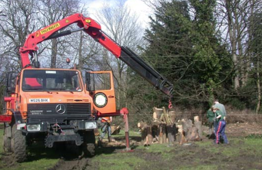 Unimog crane lifting heavy logs